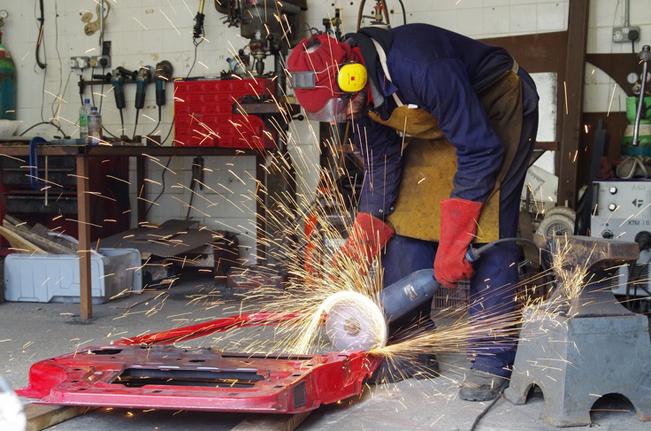 Ptlolemy Elrington trabajando en su taller con una puerta de coche de desguace